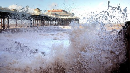 Waves smash against Cromer Pier and the sea defences more than two hours ahead of the high tide and