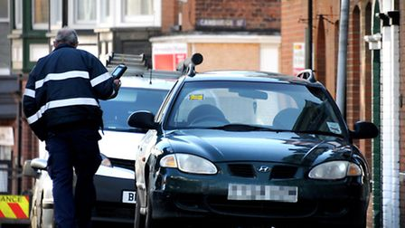 A traffic warden handing out a parking ticket on Mount Street in Cromer. The town could see an incre