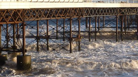 Blustery winds driving waves and foamy surf against the pier and promenade at Cromer. Picture; RICHA