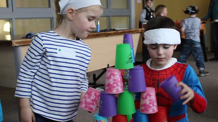 Maddie and Corbyn have a go at a cup-stacking challenge. Picture: KAREN BETHELL
