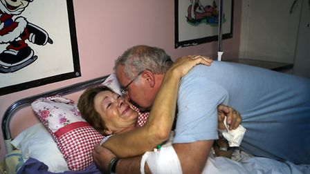 Christine Callaghan (L), one of the Sousse attacks surviviors, hugs her husband Tony at a hospital i