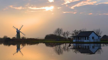 Late afternoon on the Thurne Marshes the sun shines through the mist and clouds and illuminates St B