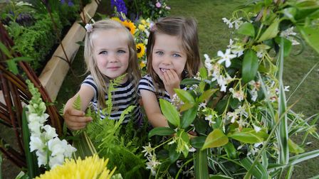 Woodgate Nursery Garden Show at Aylsham. Twins Evie and Lucia Camelford, 3, with last year's floral
