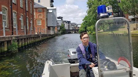 Brandon Thomas drives a Broads Authority boat on the river in Norwich. Picture: NWHS