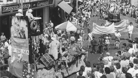 Sheringham's carnival procession, watched by large crowds, moves through the town, July 1984. Pictur