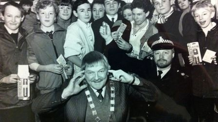 Mr McGinn handing over safety alarms to Starlings Newsagents paper deliverers in the 1980s. PHOTO: E
