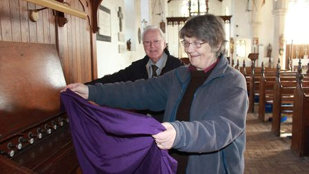 Churchwardens Helen Burrell and Colin Willis put protective sheeting over Erpingham church's organ,