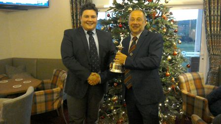 Swaffham Golf Club's Nic Cains receives his Order of Merit trophy from Norfolk PGA captain Mark Spoo