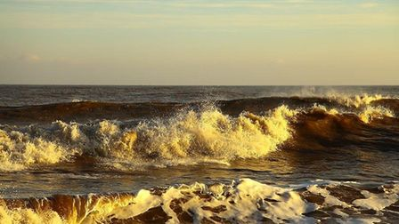 The waves break in unusual light at Cromer. Photo: Peter Chenery