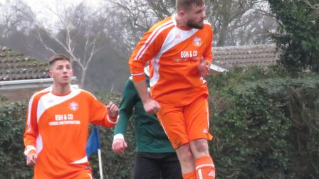 Trimingham Pilgrims' Daniel Tyrell heads clear watched by Adam Johnson. Picture: Charlotte Crane