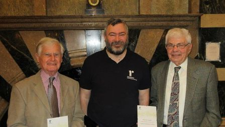 Certificates awarded to Don Davenport, left, and Dereck Smith, right, by Richard May for their servi