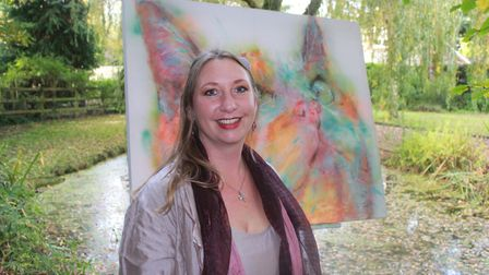 Artist Hannah Hardy with one of her rainbow-inspired paintings. Photo: KAREN BETHELL
