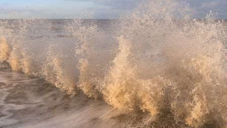 Surf hitting the breakwater at Overstrand beach, north Norfolk on a bright cold winter's morning Pho