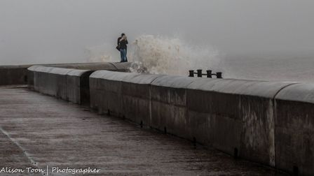 The pair are inches from a huge wave in Cromer. Picture: Alison Toon