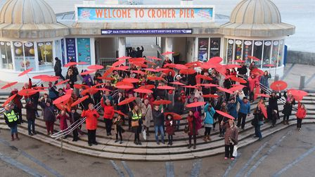 Red parasols stand out at Cromer Pier after a parade of 100 women celebrate International Women's Da