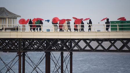 Red parasols stand out on Cromer Pier as 100 women get together to parade for International Women's