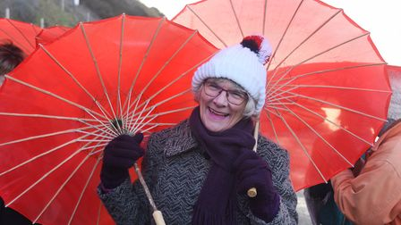 Councillor Hilary Cox with her red parasols at Cromer as 100 women get together to parade for Intern