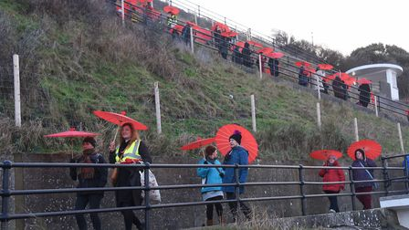 Red parasols stand out at Cromer as 100 women get together to parade for International Women's Day.