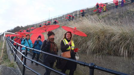 Red parasols stand out at Cromer as 100 women get together to parade for International Women's Day l