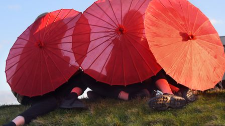 Sitting out of the wind behind their red parasols ready for the parade at Cromer as 100 women get to