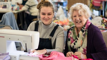 CJ Glover and Irene Palmer help make dresses for Ugandan youngsters at a 12-hour sewathon held at th