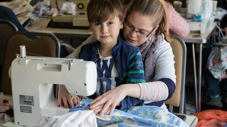 Hannah Morrison and Olly Gabriel help make dresses for Ugandan youngsters at a 12-hour sewathon held