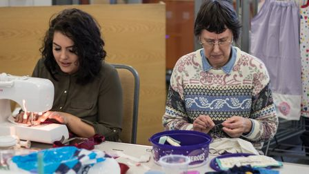 Volunteers making clothes for needy Ugandan children at a 12-hour sewathon held at the Lighthouse Co