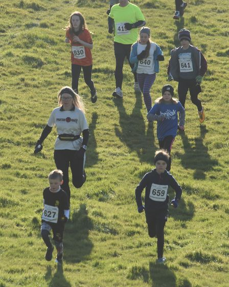 The runners downhill at the start of the Juniors race in the Hunny Bell Cross Country 2018, at the S