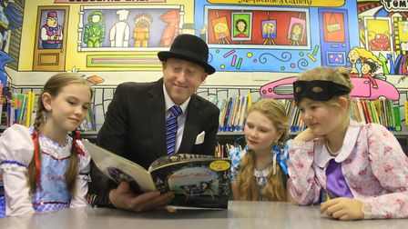Head teacher Whil De Neve (dressed as Mr Benn) shares a story with pupils in Cromer Junior School's
