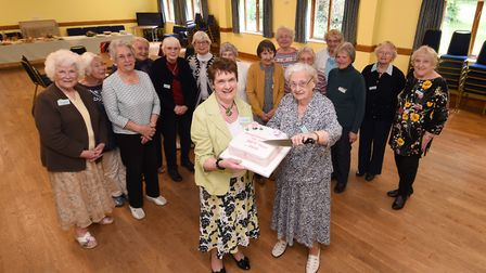 Last year's reunion. Organiser Joan Matthews, front left, cutting the cake with Jane Williams, who w