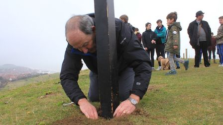 Fixing the cross in place at the top of Beeston Hilll. Photo: KAREN BETHELL