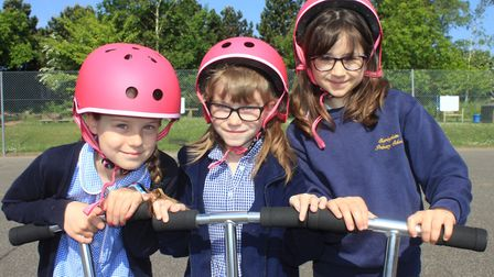 Pals Aimee, Lila and Rosetta take Sheringham Primary School's new scooters for a spin around the pla