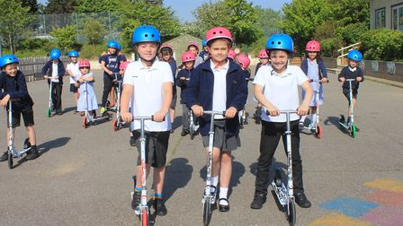 Jay Jay, Daisy and Corbyn take Sheringham Primary School's new scooters for a spin around the playgr