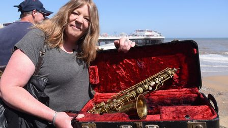 April Vogel with a 1920s gold plated Conn Saxophone she rescued from a skip, in the queue at the Ant