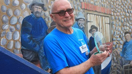 Sheringham artist Colin Seal, pictured in front of the mural he painted outside the town's seafront