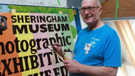 Artist Colin Seal working on display boards for Sheringham Museum's Olive Edis photography exhibitio