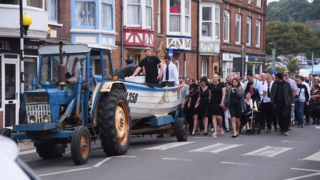 Friends and family follow the coffin in the fishing boat through Cromer for 22-year-old Adam Brown's