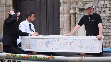 Family with 22-year-old Adam Brown's coffin in the fishing boat for his funeral at Cromer. Picture: