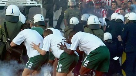 Players of Greek football club Panathinaikos cower behind riot police for protection from objects an