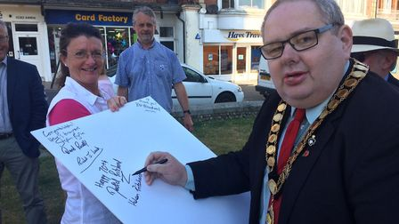 NHS 70th birthday in Cromer. David Pritchard signs the birthday card with Elaine Addison on left. P