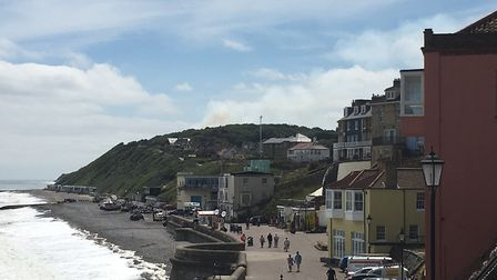 Smoke can be seen rising from the scene of the blaze near Cromer Lighthouse, as seen from the prom n