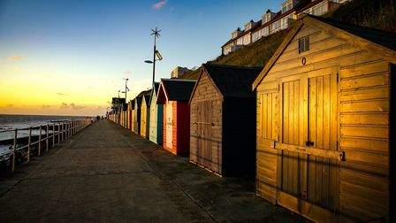 A beautiful warm dawn glow to the beach huts in Sheringham. Photo: Claire Wallace