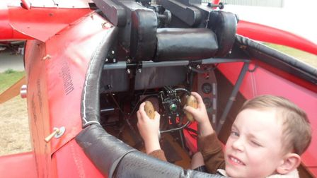 Four year-old Henry Dickenson of Overstrand inspects a replica of the First World War triplane flown