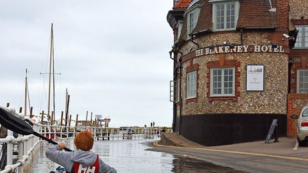 A kayaker takes to the quayside in his vessel in Blakeney at high tide. Picture: NEIL FOSTER/WATERFR