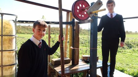 Toby Jacobs, left, and William Wickham, both 15, use the water pump at Reepham High School and Colle