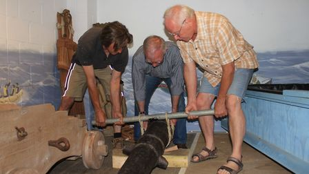 Sheringham Museum volunteers lifting a restored 7ft cannon onto a new English oak carriage based on
