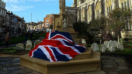 Cromer's newly-restored war memorial draped in a Union Jack before being unveiled.Photo: PETER CHENE