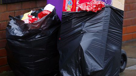 A rubbish bin overflows with wrapping paper and packaging from opened Christmas presents. Photo: Pet