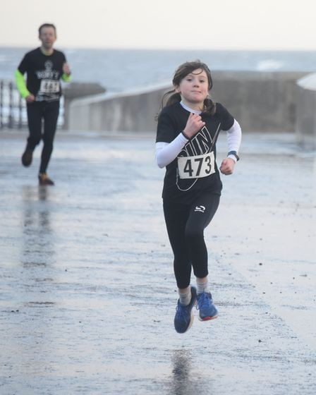 Iris Clarke, 11, in second place in the New Year's Day family fun run at Cromer. Picture: DENISE BRA