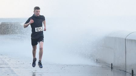 Stanley Clarke, 15, in the lead as he avoids the high tide waves over the wall during the New Year's
